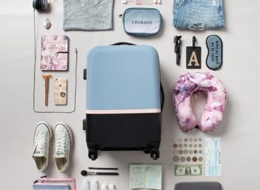 travel accessories arranged next to a suitcase